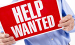 Help Wanted sign held by man.